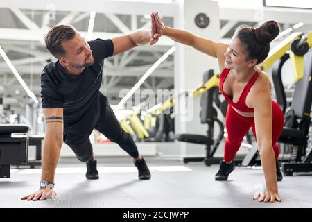 jeunes caucasiens hommes et femmes athlètes faisant des push-up pendant l'entraînement de cross à la salle de gym, donner élevé cinq l'un à l'autre