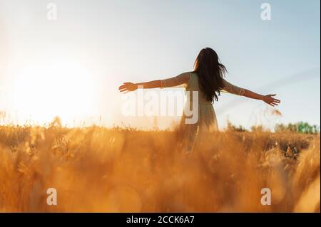 Jeune femme aux bras tendus debout au milieu d'une ferme de blé contre ciel dégagé au coucher du soleil