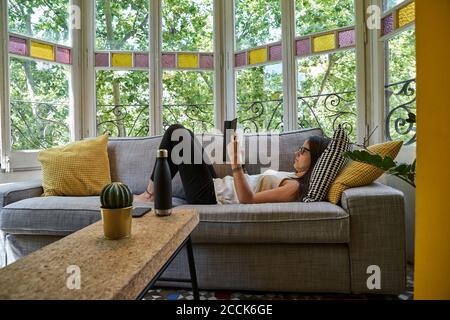 Femme lisant un livre tout en se relaxant sur un canapé dans le salon