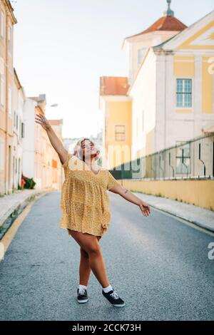 Femme aux bras étirés debout sur la route en ville
