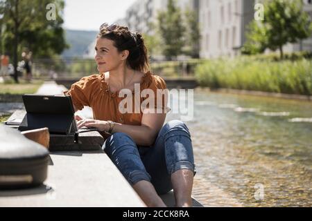 Femme attentionnés avec un ordinateur portable assis près d'un étang dans le parc pendant jour ensoleillé