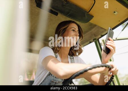 Jeune femme souriante utilisant un téléphone portable dans un tracteur