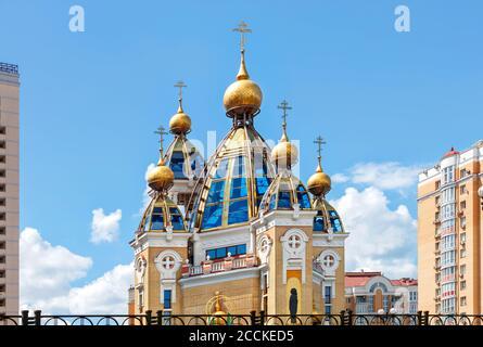 Dômes d'or d'une église chrétienne sur des façades de toit en verre au milieu d'une zone résidentielle urbaine contre un ciel bleu nuageux. Banque D'Images