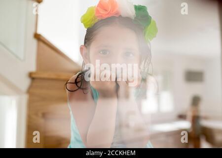Gros plan d'une jolie fille portant un tiara coloré à travers le verre à la maison Banque D'Images