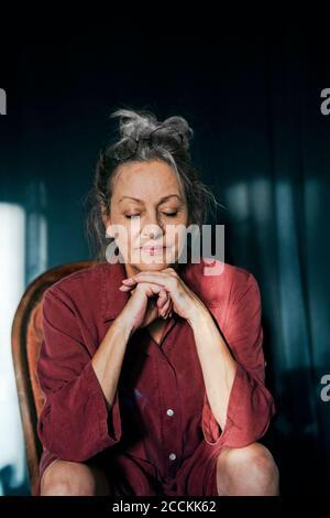 Gros plan d'une femme âgée avec les yeux fermés assis sur une chaise contre le rideau à la maison