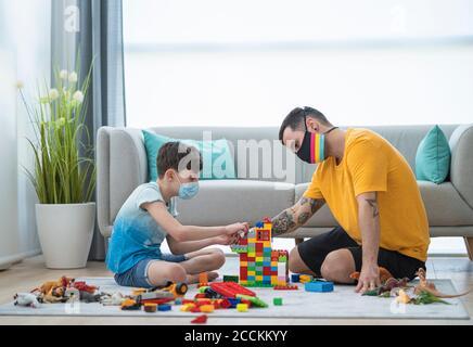 Homme et garçon portant des masques tout en organisant des blocs de jouets dans salon pendant le couvre-feu