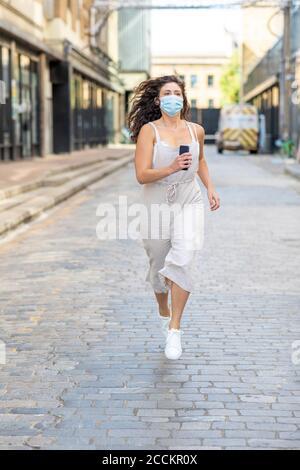 Jeune femme portant un masque courant dans la rue en ville