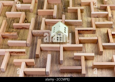 concept immobilier, modèle de labyrinthe en bois avec maison dans le centre