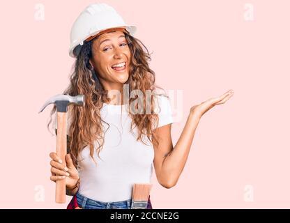 Jeune femme hispanique avec tatouage portant un casque et des vêtements de construction marteau de maintien célébrant la victoire avec un sourire heureux et l'expression du gagnant avec ra Banque D'Images