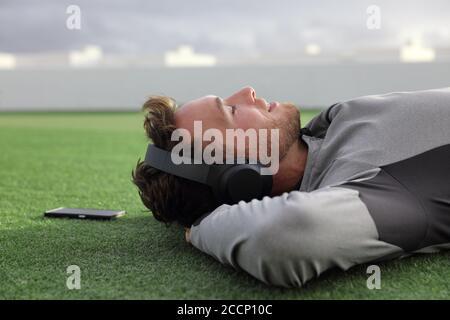 Un homme heureux qui écoute la musique du téléphone avec un casque pour dormir ou méditer sur l'herbe verte couchée en profitant de la journée d'été dans le parc. Jeune adulte Banque D'Images
