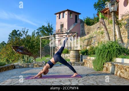 Fille faisant un chien vers le bas une jambe élever posture de yoga pendant une séance d'entraînement matinale sur un patio en pierre pavée à l'extérieur dans le jardin dans un centre de santé et de remise en forme