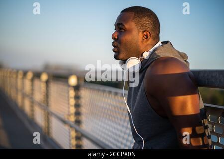 Portrait d'un jeune homme afro-américain joyeux en vêtements de sport qui se détend après le jogging. Banque D'Images