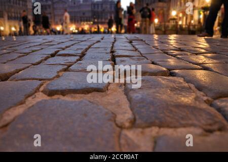 En premier plan, le sol de la Grand place (Grote Markt) à Bruxelles la nuit, en arrière-plan, hors foyer, les gens appréciant la vue de l'op