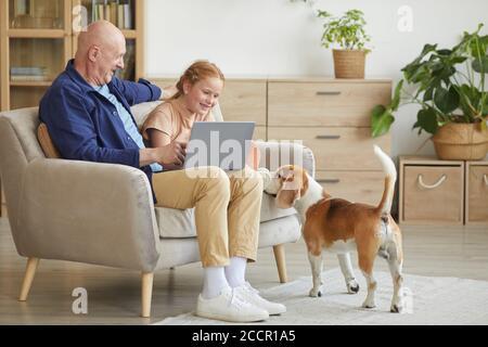 Portrait complet de l'homme moderne senior appréciant le temps à la maison avec la fille à cheveux rouges de cure et chien d'animal de compagnie, espace de copie