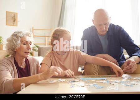 Portrait de cure fille à cheveux rouges jouant à des jeux de société avec grand-parents tout en appréciant le temps ensemble dans une maison confortable éclairée par lumière du soleil