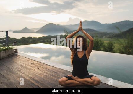 Femme méditant seule sur la piscine à débordement avec belle vue sur l'océan et la montagne le matin. Mode de vie sain, concept spirituel et émotionnel. Éveil, harmonie avec la nature.