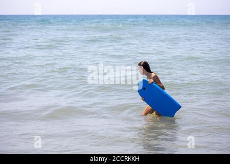 Une fille portant un bodyboard bleu sur la plage à commencez à surfer