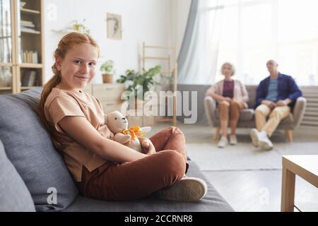 Portrait aux tons chauds d'une jolie fille à cheveux rouges regardant l'appareil photo tout en étant assise sur un canapé dans un salon confortable avec des grands-parents en arrière-plan, espace de copie