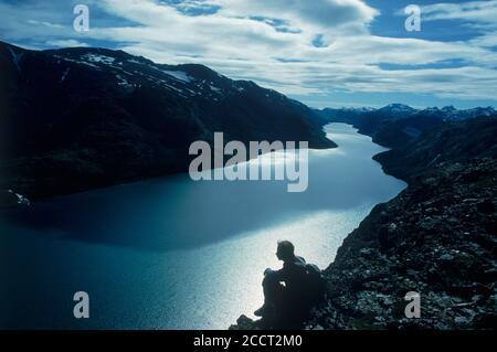 Assis au-dessus de Gjende randonneur (ou Gjendin) Lac dans les montagnes de Jotunheimen dans le parc national de Jotunheimen Banque D'Images