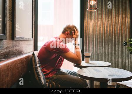 l'homme s'est assis en se sentant stressé avec son visage dans les mains dans un café