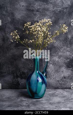 Vase en pot bleu avec fleurs blanches séchées en vrac de gitsophila sur fond de pierre texturé foncé, vue en angle