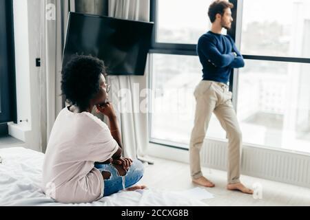 Prise de vue en intérieur d'une femme à la peau sombre se sentant seule et déprimée alors que son petit ami caucasien se tient à côté de la fenêtre panoramique et regarde à l'extérieur. Réf Banque D'Images