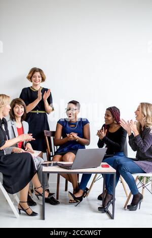 De l'équipage féminin multiraciale des collègues regardant la vidéo sur netbook pour nouveau projet d'affaires faire de la recherche, bénéficiant d'unité et des émotions positives Banque D'Images