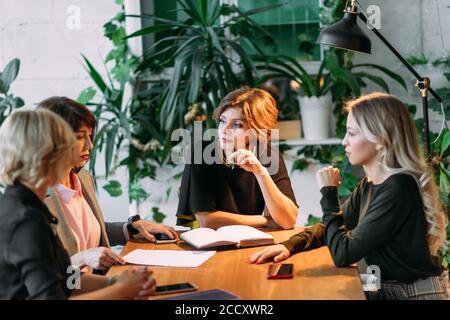 Groupe d'younghardworking les jeunes femmes travailler tard le soir dans la salle de réunion d'essayer de remplir leurs missions.