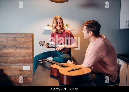 jeune femme caucasienne attrayante en tenue décontractée jouant ukulele pour homme l'écoutant Banque D'Images
