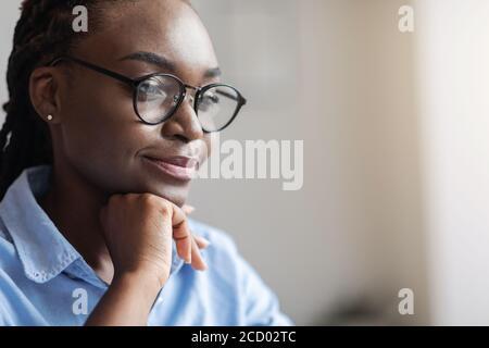 Gros plan portrait de la femme entrepreneur noire pensive en lunettes de vue de côté