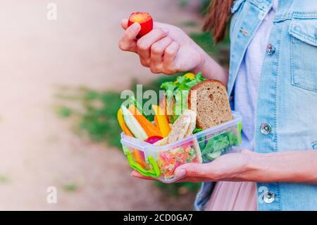 Concept de nourriture saine: Jeune fille hipster manger à partir de la boîte à déjeuner rempli de sandwich, pain croustillant, fruits et légumes assis sur les escaliers à l'extérieur. Sél Banque D'Images