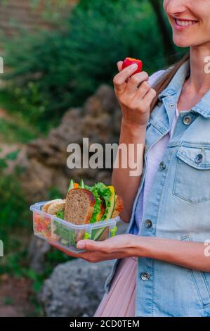 Concept de nourriture saine : jeune fille de hipster manger à partir de la boîte à lunch remplie de sandwich, pains croustillants, fruits et légumes à l'extérieur Banque D'Images