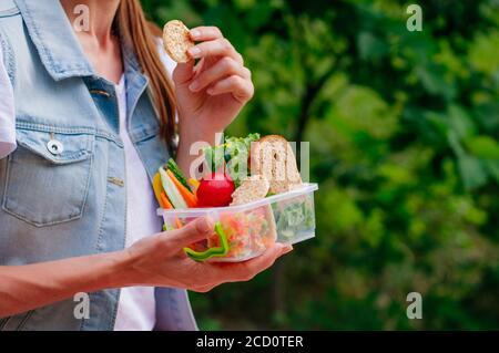 Concept de nourriture saine : jeune fille de hipster manger à partir de la boîte à lunch remplie de sandwich, pains croustillants, fruits et légumes à l'extérieur. Mise au point sélective sur lu Banque D'Images