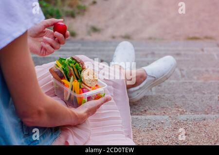 Concept de nourriture saine: Jeune fille hipster manger à partir de la boîte à déjeuner rempli de sandwich, pain croustillant, fruits et légumes assis sur les escaliers outddor. Sél Banque D'Images