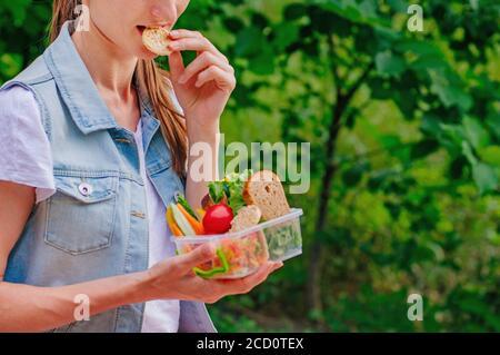 Concept de nourriture saine : jeune fille de hipster manger à partir de la boîte à lunch remplie de sandwich, pains croustillants, fruits et légumes à l'extérieur. Banque D'Images