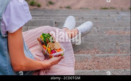 Jeune fille de hipster manger à partir de la boîte à déjeuner remplie de sandwich, pain croustillant, fruits et légumes assis sur les escaliers à l'extérieur. Accent sélectif sur le déjeuner Banque D'Images