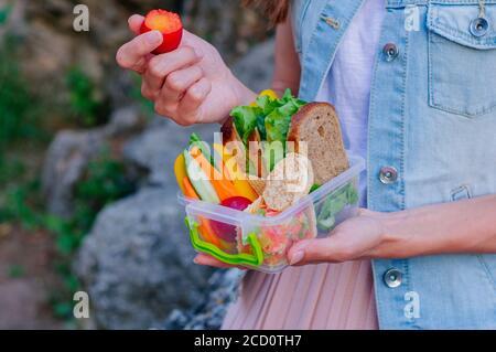 Concept de nourriture saine: Jeune fille hipster mangeant la prune de la boîte à lunch remplie de sandwich, pains croustillants, fruits et légumes à l'extérieur. Mise au point sélective Banque D'Images