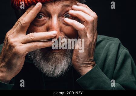 Un homme barbu âgé qui a l'air extrêmement surpris ou effrayé, protégeant son visage avec les mains, gros plan portrait du visage sur fond noir de studio.