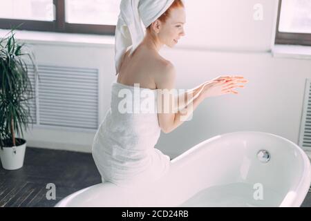 Belle femme en bain va laver son corps dans la baignoire à la maison, vérifier l'eau avec la main, profiter de minutes de tranquillité et de silence Banque D'Images