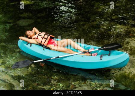 Une femme heureuse se détendre en étant couchée en kayak sur le lac