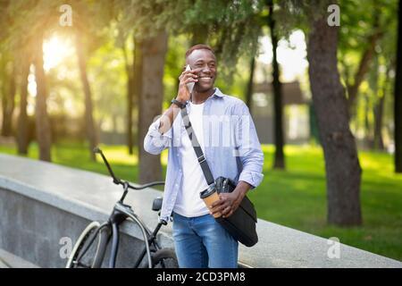 Jeune homme noir avec un café à emporter près de son vélo au parc et à parler au téléphone portable Banque D'Images