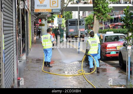 Les travailleurs du Département de l'hygiène alimentaire et environnementale (FEHD) nettoient un trottoir sur le chemin Lockhart, WAN Chai, Hong Kong. Banque D'Images