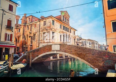 Pont en pierre Ponte Caneva traversant le canal de Vena avec des bateaux amarrés et un vieux bâtiment dans le centre historique de la ville de Chioggia, ciel bleu en été, région de Vénétie, Italie du Nord