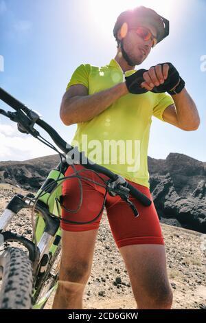 Cycliste regardant la montre intelligente tout en pédalant sur route. Athlète cycliste utilisant le tracker d'activité montre de fitness gps sur l'entraînement de vélo au coucher du soleil