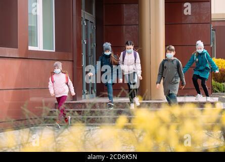 Les enfants des élèves qui se trouvent dans un masque médical quittent l'école.