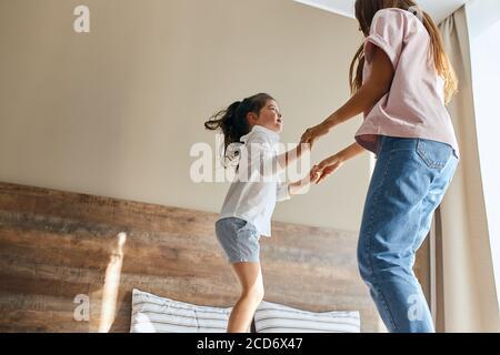 Jeune mère et petite fille s'amuser à la maison, jouer ensemble, sauter au lit, passer des vacances ensemble, concept de temps en famille Banque D'Images