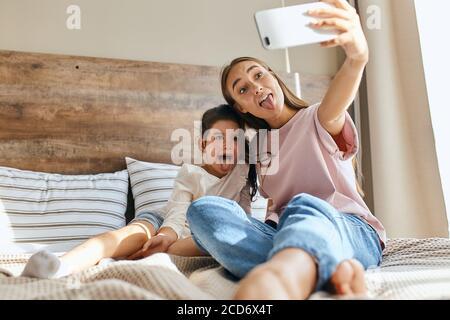 Deux belles filles ayant l'amusement dans la chambre, la femme attrayante prend des photos en utilisant le téléphone cellulaire, montrant la langue pleine de joie, le fond de petits oreillers, le tremblement