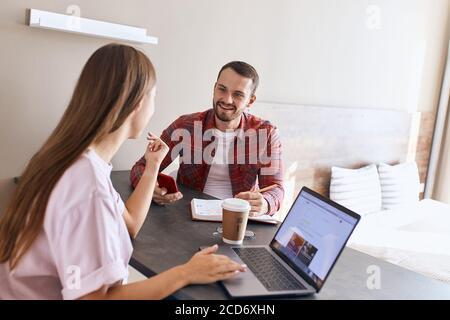 Charmant jeune couple parlant dans une chambre lumineuse, assis à une table sombre, discutant de tâches quotidiennes, utilisant des appareils, concept de famille Banque D'Images
