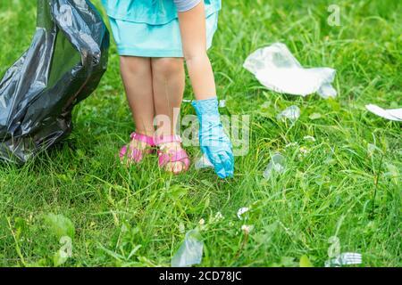 Une petite fille nettoie les déchets en plastique sur l'herbe verte le parc Banque D'Images
