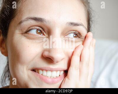 Jeune femme latine souriant avec la main sur son visage regardant de côté